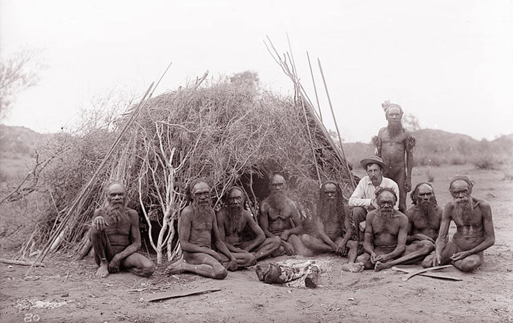 Fig. 11. Une communauté aborigène devant une habitation. Longues sagaies de chasse et de guerre appuyées contre la hutte. Au sol des boomerangs. (http://carreephemere.blogspot.ch/2017/03/architecture-du-monde-laustralie.html)